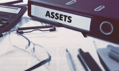 Assets - Office Folder on Background of Working Table with Stationery, Glasses, Reports. Business Concept on Blurred Background. Toned Image.