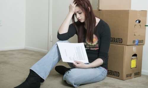 Woman who appears sad with moving boxes and eviction note