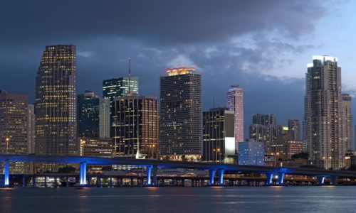 Miami city skyline at dusk. Urban skyscrapers and bridge over the sea with reflections.