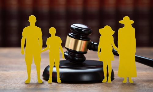 Closeup of paper family with mallet on table in courtroom